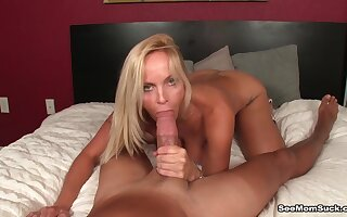 Denuded MILF stands nude and throats a generous cock while being taped